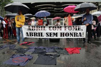 Manifestantes estenderam os uniformes surrados em frente à gráfica simbolizando sua dedicação à empresa que agora dá o calote. Foto: Cadu Bazilevski/SJSP